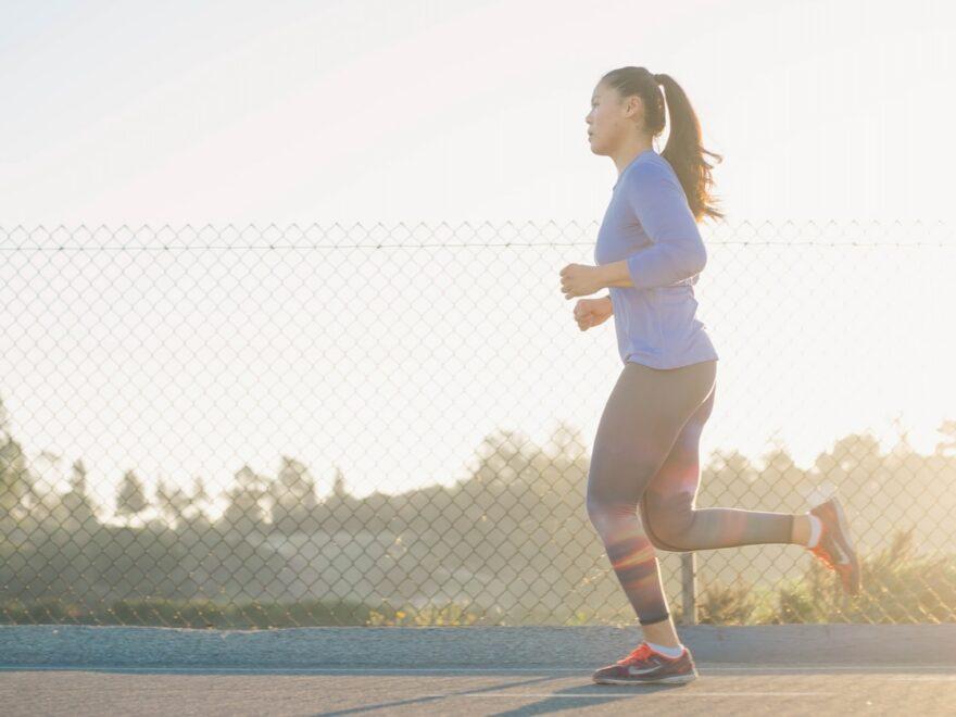 woman jogging near wire fence
